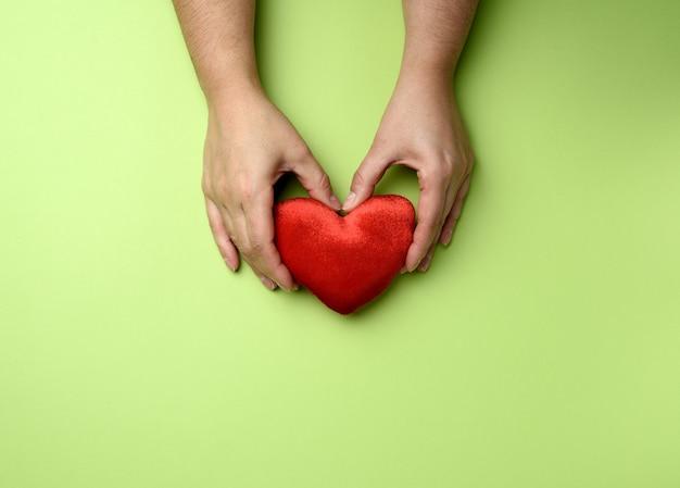 Le mani femminili tiene il cuore rosso della tessile sul verde