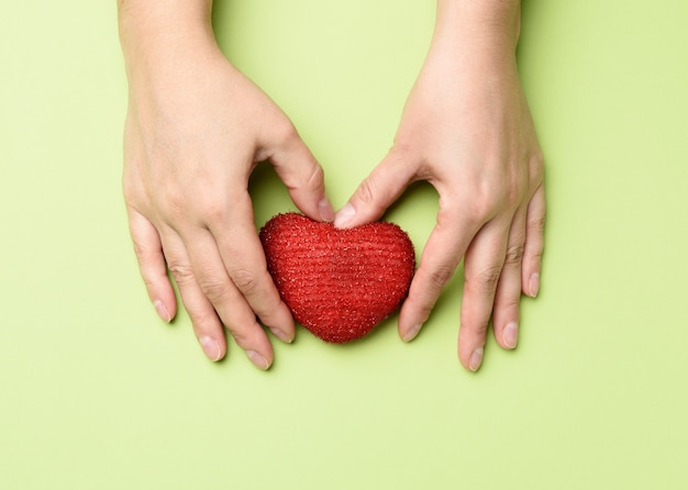 Le mani femminili tengono il cuore rosso della tessile amore e donazione