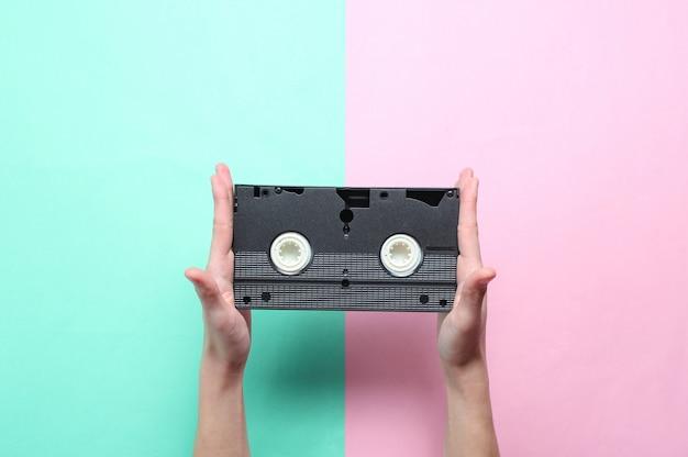 Le mani femminili tiene la videocassetta su fondo pastello blu rosa. stile retrò, cultura pop, minimalismo, vista dall'alto