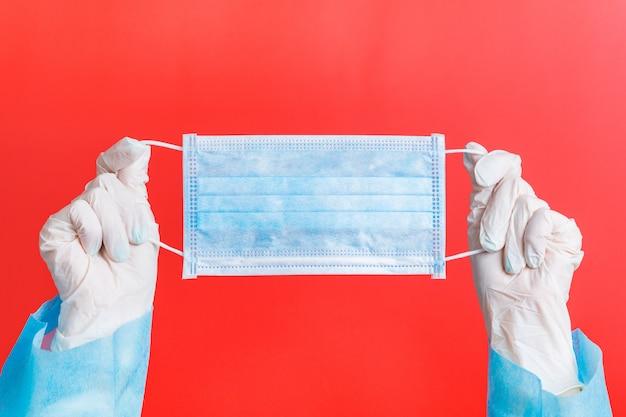Mani femminili in guanti medici che tengono maschera protettiva al rosso. concetto di assistenza sanitaria. concetto di coronavirus