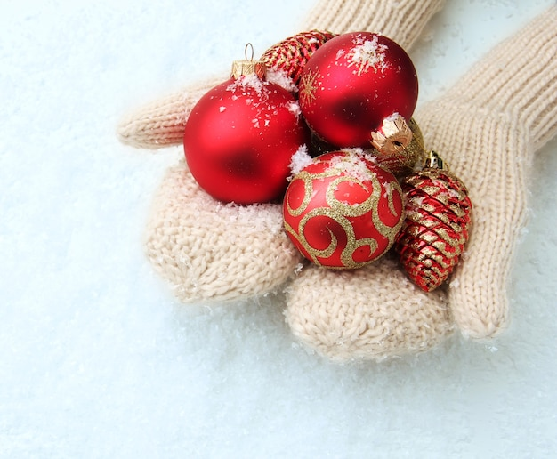 Mani femminili in guanti palle dell'albero di natale, su sfondo colorato