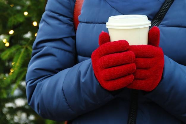 Mani femminili in guanti con il primo piano della tazza di caffè