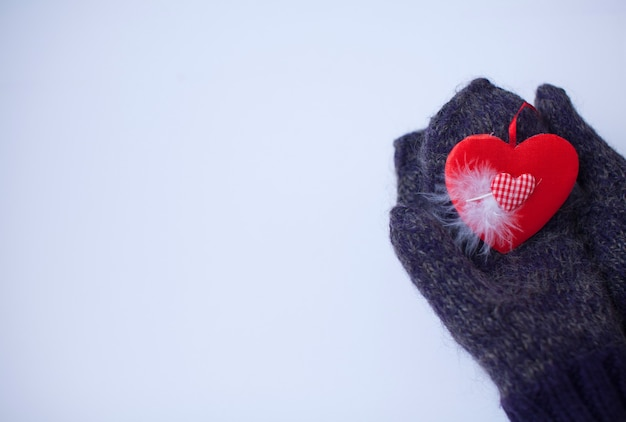 Mani femminili in guanti con cuore rosso, primo piano