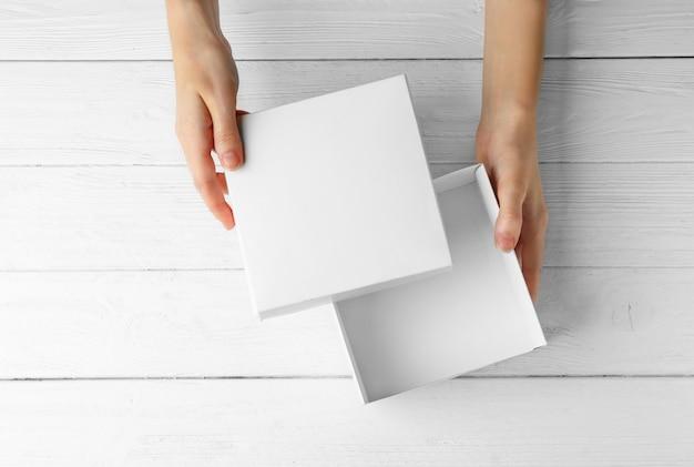 Mani femminili che aprono scatola bianca, su fondo di legno