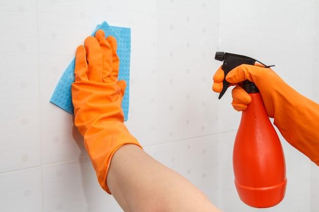 Le mani femminili in guanti di gomma arancione tengono una bottiglia di detersivo e un tovagliolo in microfibra blu. la donna sta lavando il muro con piastrelle bianche in bagno. strumenti e attrezzature per la pulizia