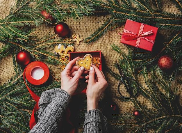 Mani femminili che confezionano biscotti in una scatola accanto alla decorazione di natale