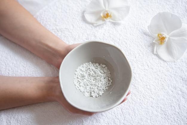 In mani femminili un piatto con vista dall'alto di una maschera cosmetica all'argilla