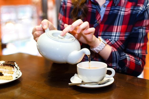 Le mani femminili hanno versato il primo piano del tè verde