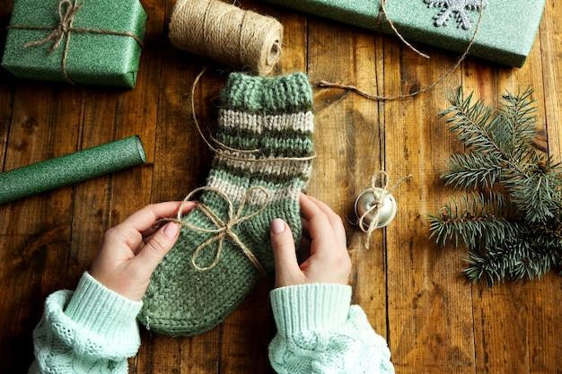 Mani femminili che preparano i regali per natale sulla tavola di legno
