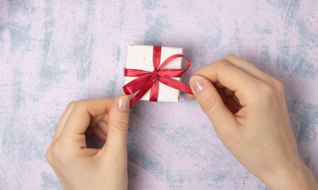 Mani femminili tirano un nastro rosso su una confezione regalo su uno sfondo chiaro. auguri di natale e capodanno o di stagione. messa a fuoco selettiva