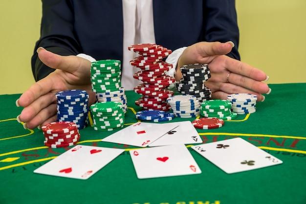Mani femminili che raggiungono per fiches da poker, carte da gioco nel casinò