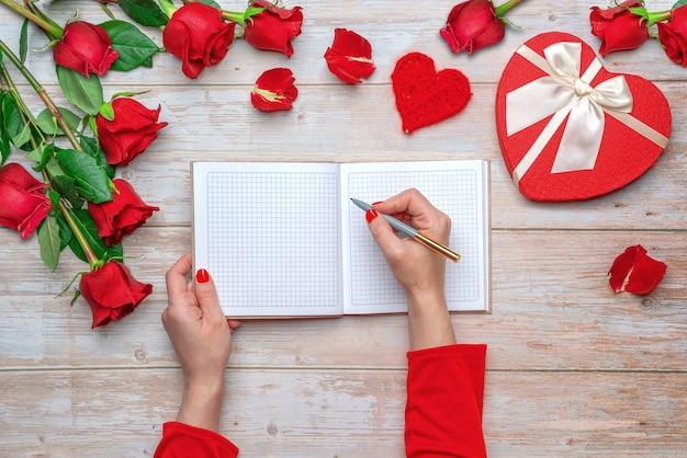 Mani femminili in maniche rosse pronte a scrivere in un quaderno a quadri con copertina rigida