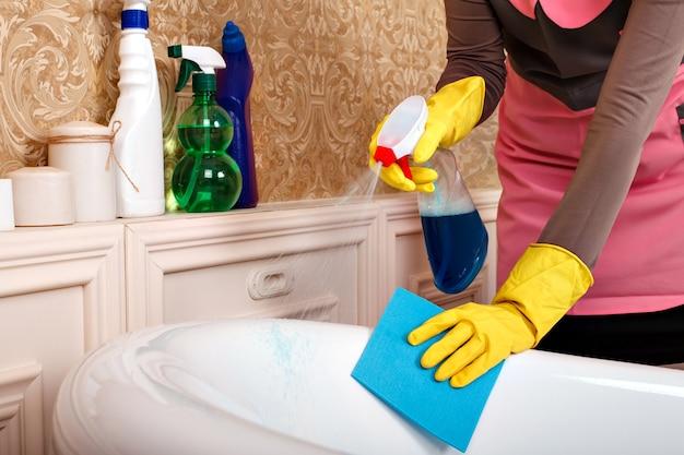 Le mani femminili in guanti di gomma puliscono il bagno.