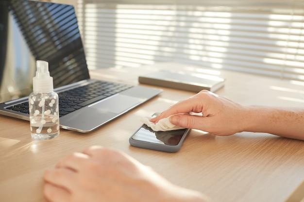 Mani femminili sanificazione smartphone mentre si lavora alla scrivania in ufficio post pandemia