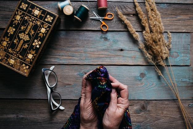 Mani femminili cucito sul tavolo di legno, forbici, scrigno, filo, bicchieri