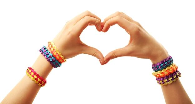 Mani femminili a forma di cuore con bracciali isolati su bianco