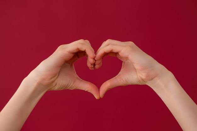 Mani femminili che mostrano il segno del cuore su sfondo rosso in studio