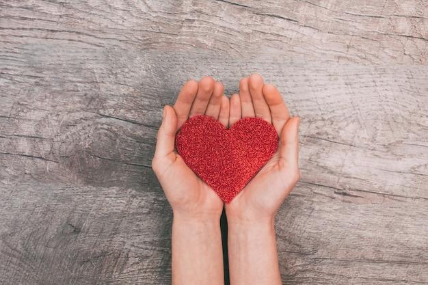 Mani femminili che mostrano cuore di carta rosso, su fondo di legno