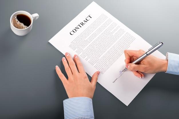 Le mani femminili firmano il contratto. primo piano del contratto di firma della donna di affari. caffè mattutino e scartoffie. finalmente una decisione intelligente.