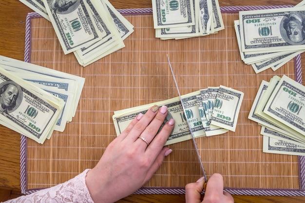 Mani femminili che affettano banconote in dollari su tappetino di bambù bamboo