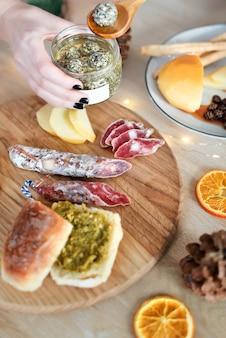Mani femminili che spalmano la crema di formaggio sul pane fresco