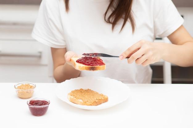Mani femminili spalmano marmellata di lamponi sul pane, preparano panini al mattino a casa per la colazione per tutta la famiglia