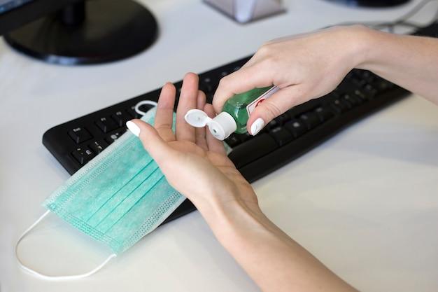 Le mani femminili schiacciano il gel del prodotto disinfettante della mano dalla bottiglia sul fondo della tastiera