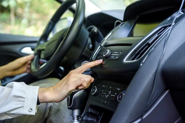 Mani femminili sul volante di un'auto. autista donna, interni auto