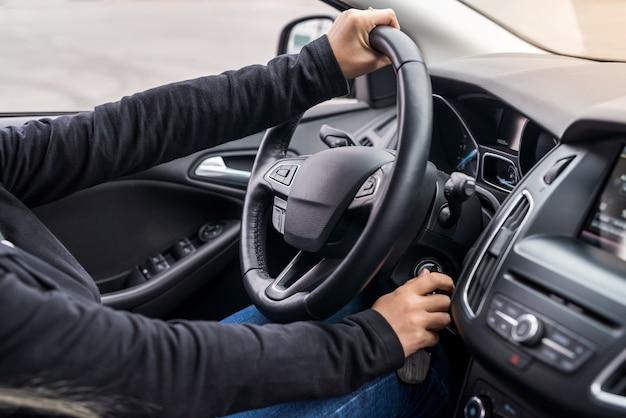 Mani femminili sul volante che avvia una macchina