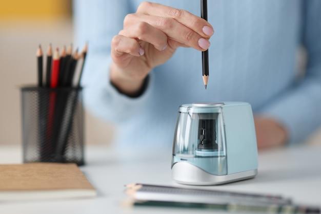 Mani femminili sporgenti matita in primo piano elettronico temperamatite. sviluppo del progetto di design