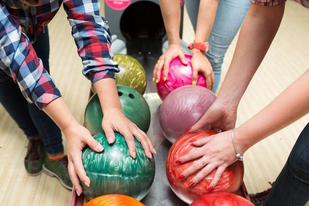 Mani femminili prendono palle da bowling.