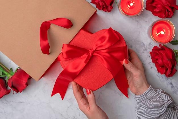 Le mani femminili tirano fuori un regalo a forma di cuore da una borsa della spesa
