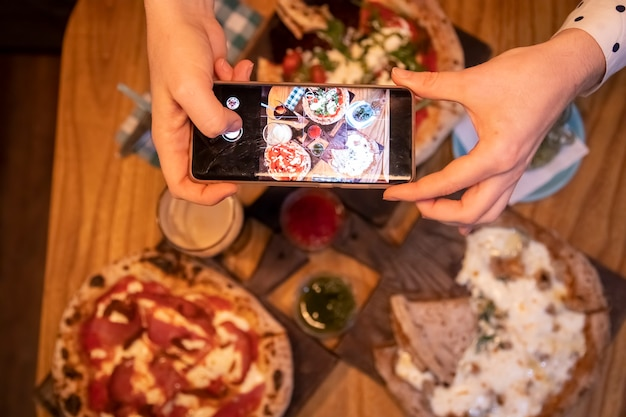 Le mani femminili scattano foto sul tavolo di uno smartphone con una deliziosa pizza in un ristorante. vista dall'alto