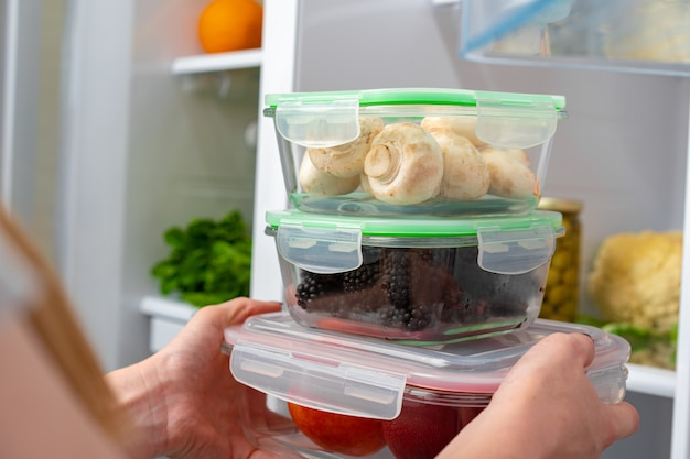 Mani femminili che prendono la scatola di immagazzinaggio con il cibo da un frigorifero