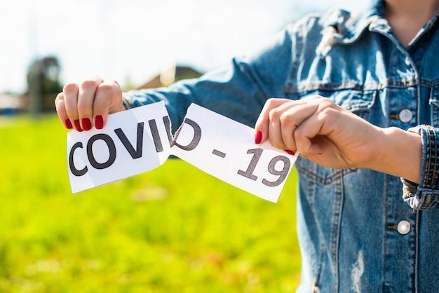 Mani femminili strappano l'iscrizione covid-19. il coronavirus è terminato.