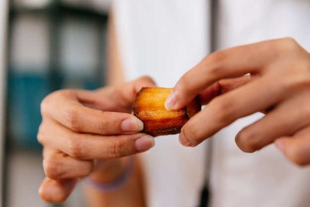 Mani femminili che strappano canelés al forno fresco.