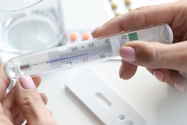 Il termometro delle mani femminili sul bicchiere d'acqua da tavola e il test pcr hanno aumentato la temperatura corporea
