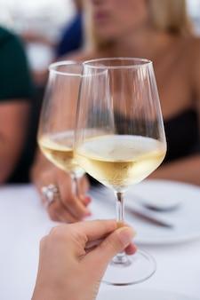 Mani femminili che tostano con bicchieri di vino bianco, primo piano