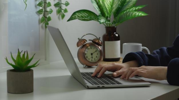 Mani femminili che digitano sul computer portatile nel design degli interni dell'area di lavoro biophilia a casa