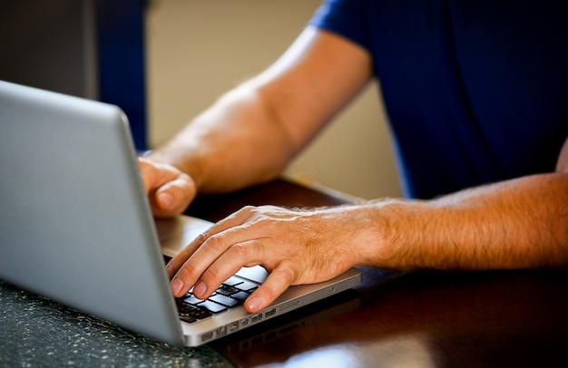 Mani femminili che digitano sulla tastiera del computer portatile in ufficio, a casa