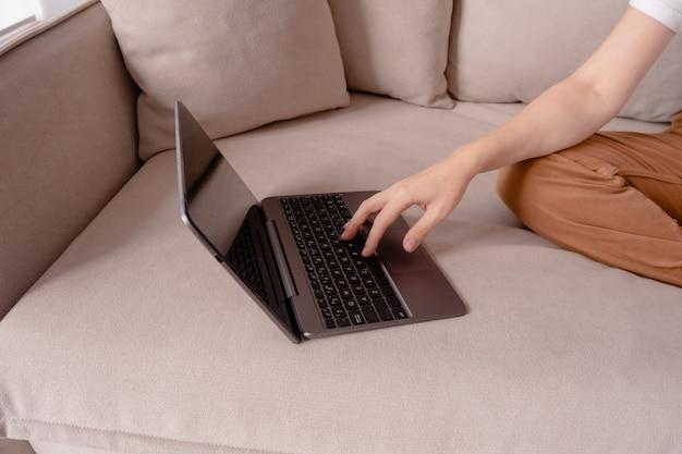 Mani femminili che digitano su un computer portatile.