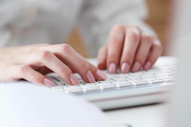 Mani femminili che digitano sulla tastiera d'argento utilizzando il computer