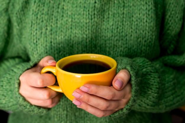 Le mani femminili in un maglione verde caldo tengono una tazza di caffè