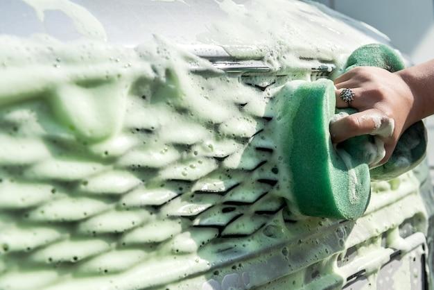 Mani femminili che lavano l'auto utilizzando una spugna per lavaggio auto con schiuma sulla stazione di lavaggio auto