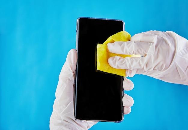 Le mani femminili in guanti medici bianchi disinfettano lo schermo di un telefono cellulare su un blu