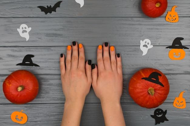 Mani femminili con manicure autunnale su uno sfondo grigio con zucche arancioni