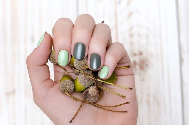 Mani femminili con un bel design verde delle unghie