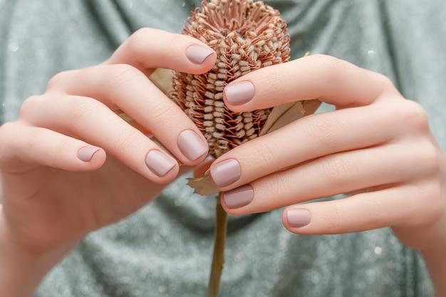 Mani femminili con design delle unghie beige. mani femminili che tengono fiore autunnale marrone. mani della donna sul fondo del tessuto d'argento.