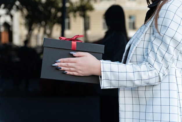 Mani femminili con confezione regalo nera con fiocco rosso. la donna prende un regalo. primo piano, vista laterale.
