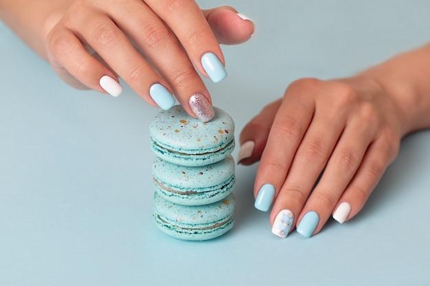 Mani femminili con unghie manicure blu che tengono amaretti dolci